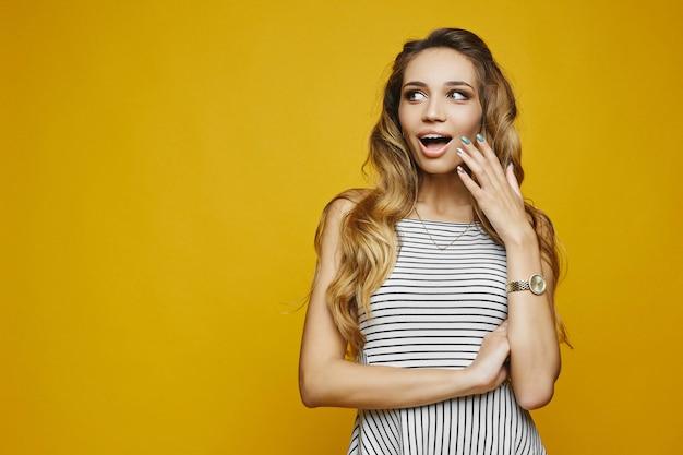 Portret van verrast model meisje poseren met open mond, haar gezicht aan te raken en kijkt opzij