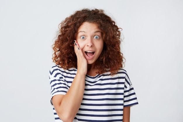 Portret van verrast opgewonden schattige jonge vrouw met krullend haar en geopende mond draagt gestreept t-shirt