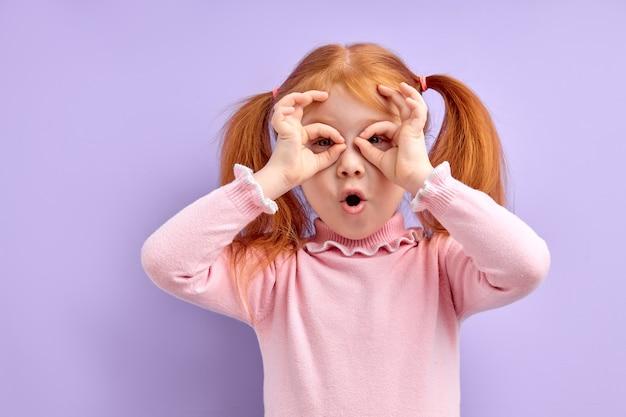 Portret van verrast schattig klein meisje kind staande geïsoleerd op paars
