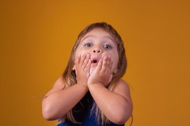 Portret van verrast schattig klein peuter meisje kind staande geïsoleerd over gele achtergrond. camera kijken. handen dichtbij open mond