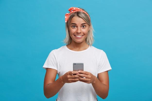 Portret van verrast schattige blonde jonge vrouw draagt witte t-shirt