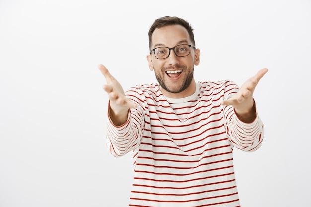 Portret van verrast tevreden volwassen man die vriend ziet en handen naar trekt