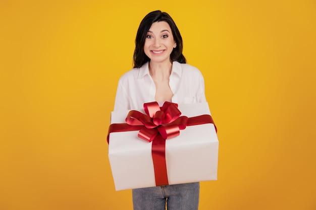 Portret van verrast vrolijk meisje houdt je cadeau op gele achtergrond
