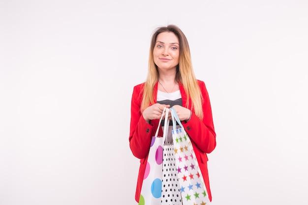 Portret van verrast vrouw in rood pak met boodschappentassen met kopie ruimte.