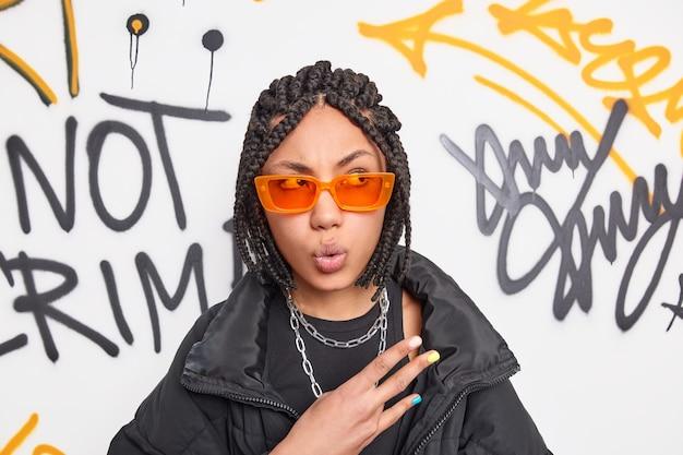 Portret van verrast vrouwelijke rapper met vlechten maakt cool gebaar kijkt afgevraagd opzij draagt trendy oranje tinten geniet van tijd buiten doorbrengen