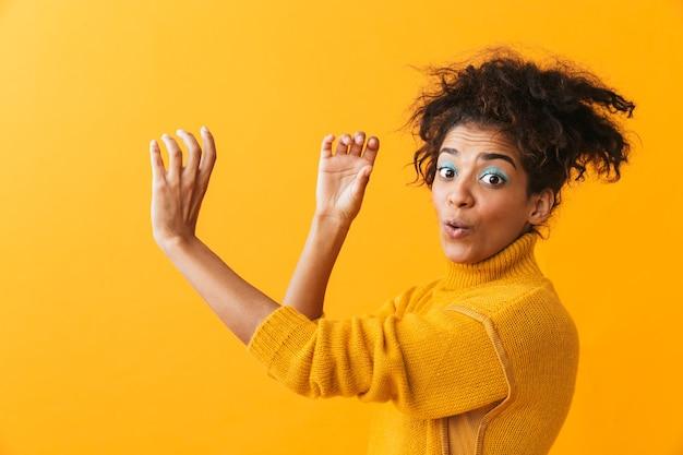 Portret van verraste afro-amerikaanse vrouw die met afrokapsel door onzichtbare geïsoleerde kijker kijkt