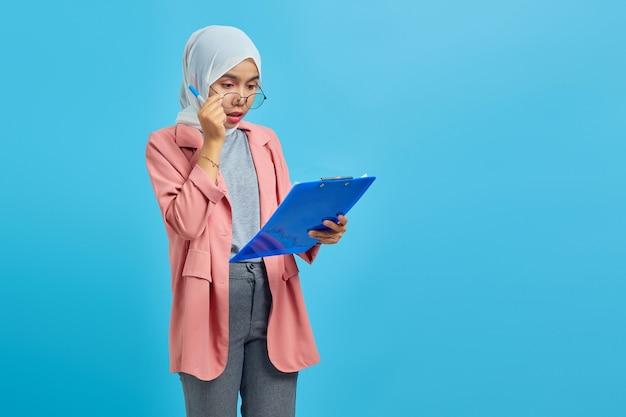 Portret van verraste aziatische vrouw die klembord op blauwe achtergrond onderzoekt