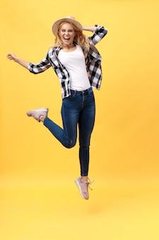 Portret van verraste jonge vrouw die in zwarte broek voor gele muur springt.