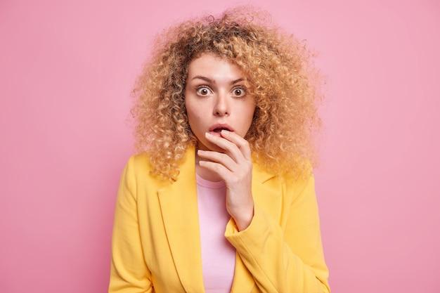 Portret van verraste jonge vrouw met krullend borstelig haar staat in een hinderlaag gelokt staart sprakeloos met geschrokken uitdrukking hoort schokkend ongelooflijk nieuws