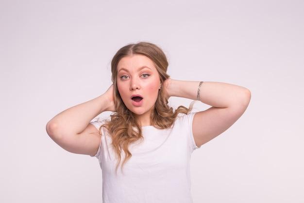 Portret van verraste jonge vrouw met krullend haar in wit t-shirt.