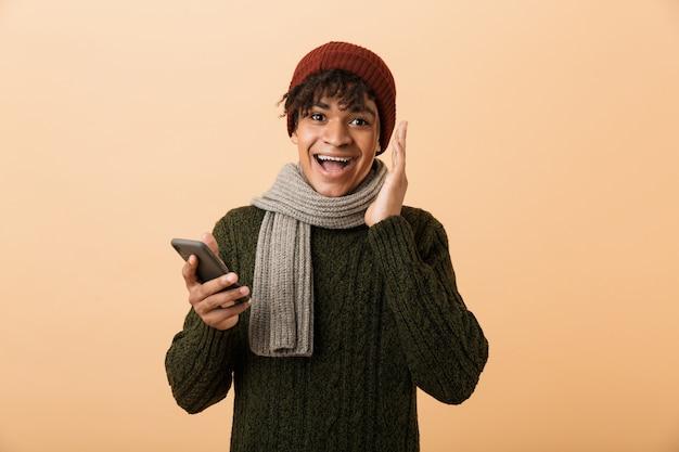 Portret van verraste tienerkerel die hoed en sjaal draagt die smartphone met behulp van, over gele muur wordt geïsoleerd