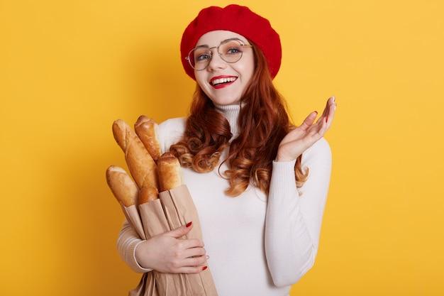Portret van verraste vrouw die baret, overhemd en eyewears op geel draagt
