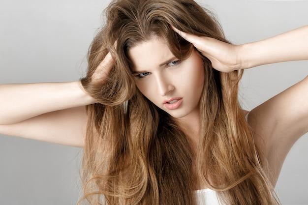 Portret van verstoorde jonge vrouw met lang haar.