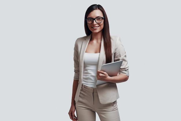 Portret van vertrouwen. aantrekkelijke jonge vrouw die naar de camera kijkt en glimlacht terwijl ze tegen een grijze achtergrond staat