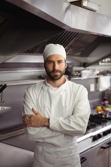 Portret van vertrouwen chef-kok permanent met armen gekruist in commerciële keuken