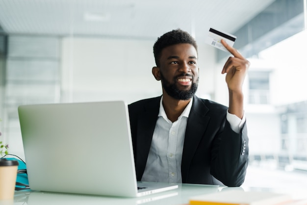 Portret van vertrouwen jonge afrikaanse man met creditcard met laptop betalen via internet