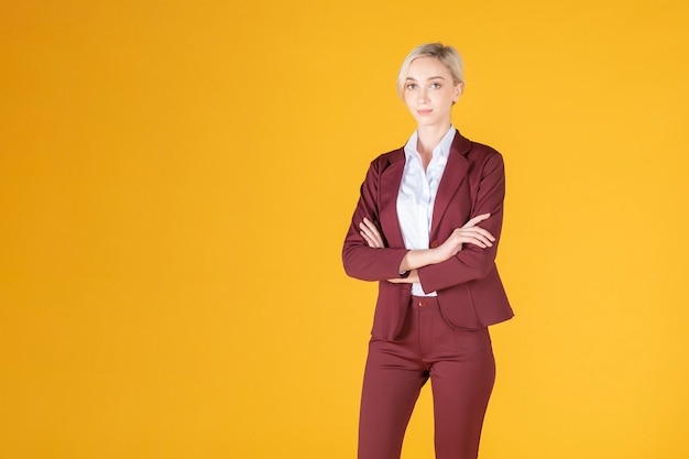 Portret van vertrouwen kaukasische bedrijfsvrouw op gele achtergrond