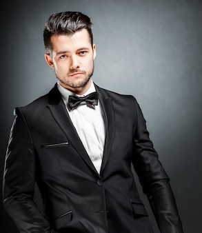 Portret van vertrouwen knappe man in zwart pak met bowtie