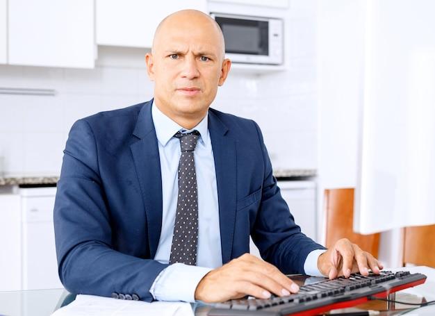 Portret van vertrouwen manager zit aan bureau en camera kijken.