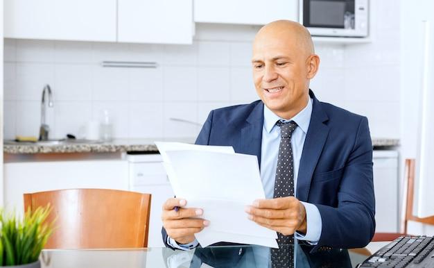 Portret van vertrouwen manager zit aan bureau en houdt een map met documenten