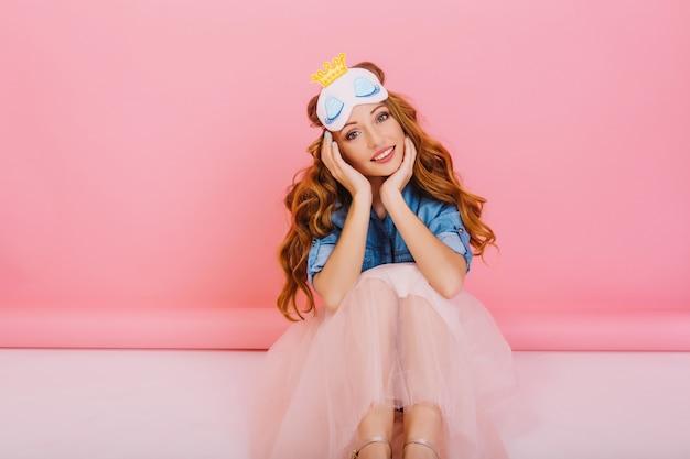 Portret van verveeld krullend meisje met mooie gezichtsuitdrukking die slaapmasker en trendy weelderige rok draagt, geïsoleerd op roze achtergrond. schattige jonge vrouw in stijlvolle outfit zittend op de vloer in haar kamer