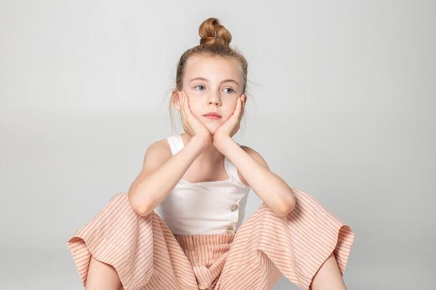 Portret van verveeld meisje in studio met wit