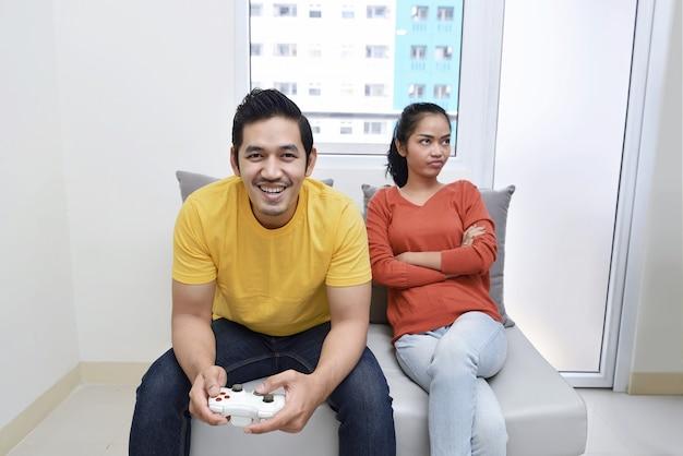 Portret van verveelde aziatische vrouw terwijl haar vriend videospelletjes spelen