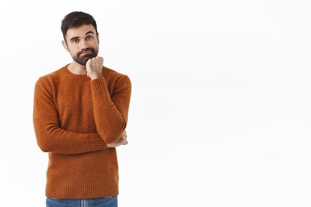 Portret van verveelde en onwillige bebaarde knappe man die op vrouw wacht in winkelcentrum terwijl hij nieuwe kleren koopt, grijns en leunt op palm, onverschillig, saaie film kijken