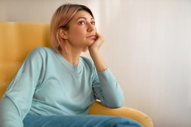 Portret van verveelde jonge vrouw met roze bob kapsel zittend op gele bank thuis met hand onder haar wang
