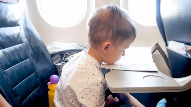 Portret van verveelde kleine peuterjongen tijdens een lange vlucht in het vliegtuig.