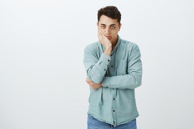 Portret van verveelde pissige aantrekkelijke mannelijke student in overhemd