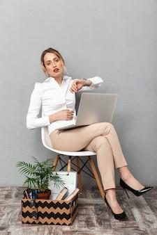Portret van verveelde vrouw met behulp van laptop zittend in een stoel met kantoor dingen, geïsoleerd