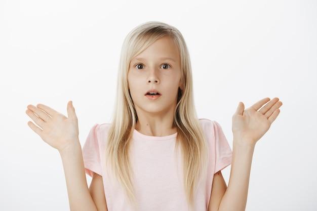 Portret van verward bezorgd schattig klein meisje met blond haar, adem ingehouden en geschokt starend, handpalmen opheffend, verrast of verbaasd door verwarrende situatie over grijze muur
