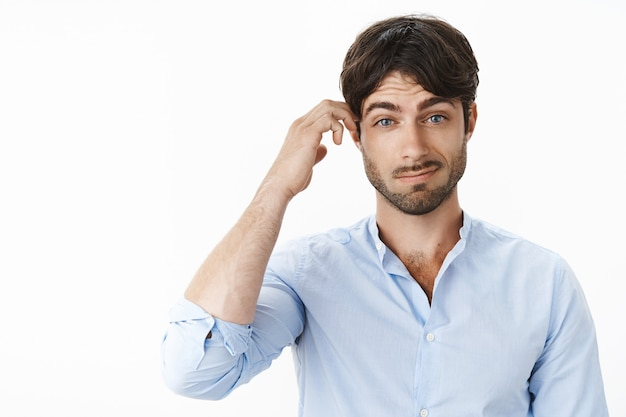 Portret van verward en geen idee, knappe vriend met blauwe ogen en baard kan hints vrouw niet begrijpen die grijnzend haar hoofd krabt terwijl ze naar voren wordt ondervraagd over grijze muur
