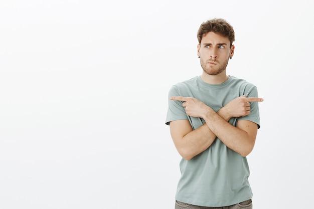 Portret van verward europees mannelijk model in oorbellen, grijnzend en fronsend tijdens het denken, handen kruisen en naar links en rechts wijzen bij het kiezen van richting