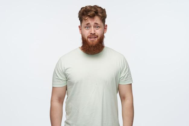 Portret van verward geïrriteerde jonge bebaarde man met rood haar, draagt een blanco t-shirt op wit