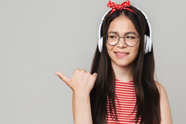 Portret van verward jong ontevreden tienermeisje gekleed in fel rood t-shirt geïsoleerd over grijze muur luisteren muziek met koptelefoon wijzend naar copyspace.