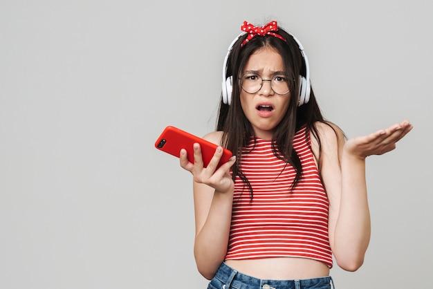 Portret van verward jong ontevreden tienermeisje gekleed in fel rood t-shirt met behulp van mobiele telefoon geïsoleerd over grijze muur luisteren muziek met koptelefoon.