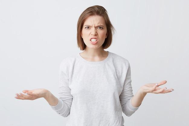 Portret van verwarde, boos jonge vrouw in longsleeve kijkt verbaasd