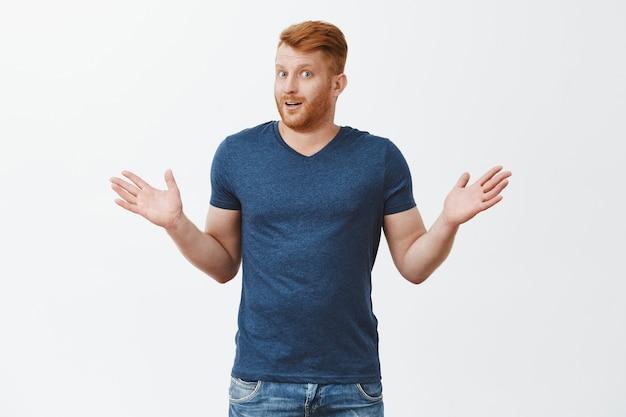 Portret van verwarde en onwetende vriendelijk ogende mannelijke man met rood haar en borstelharen, schouderophalend met opgeheven handpalmen en onzeker en onbewust starend