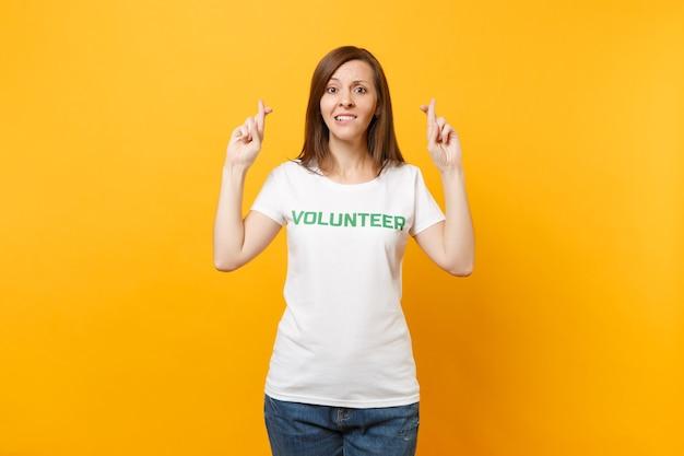 Portret van verwarde hoop bezorgde vrouw in wit t-shirt met geschreven inscriptie groene titel vrijwilliger geïsoleerd op gele achtergrond. vrijwillige gratis hulp, liefdadigheidswerkconcept.