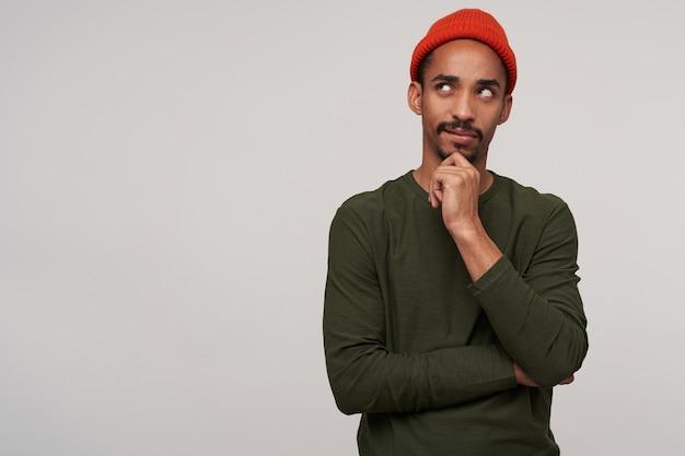 Portret van verwarde jonge vrij donkere man met baard met opgeheven hand op zijn kin en bedachtzaam naar boven kijkend, geïsoleerd op wit
