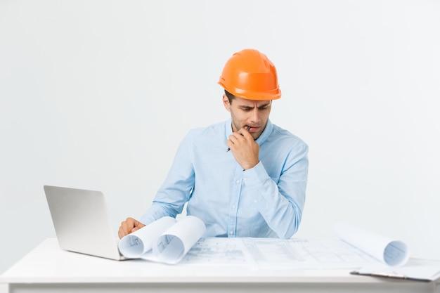 Portret van verwarde mannelijke ontwerper of architect, voelt zich gestrest, nerveus, houdt hand op het hoofd, staart in blauwdruk. uitgeputte man creëert bouwproject alleen, heeft wat problemen.