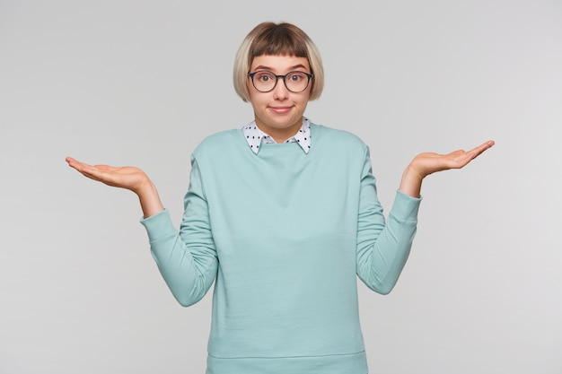 Portret van verwarde mooie jonge vrouw draagt blauw sweatshirt