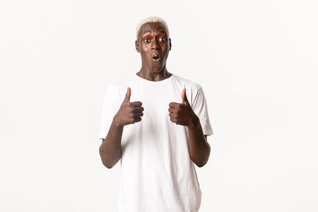 Portret van verwonderde en onder de indruk afro-amerikaanse blonde man, gefascineerd duimen omhoog