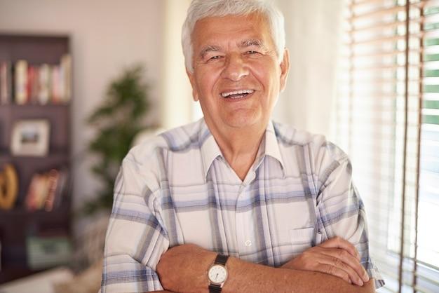 Portret van vitale oude man in de woonkamer