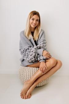 Portret van volledige lengte van mooie gelukkige vrouw met blond haar en lange mooie benen die pullover dragen die over geïsoleerde muur zitten