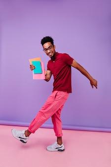 Portret van volledige lengte van vrolijke internationale student die na examens danst. slimme afrikaanse man in roze broek permanent met boeken.