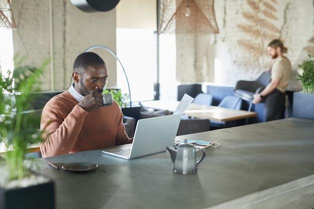 Portret van volwassen afro-amerikaanse man die laptop gebruikt en geniet van koffie terwijl hij werkt in een milieuvriendelijk café-interieur versierd met verse groene planten, kopieer ruimte