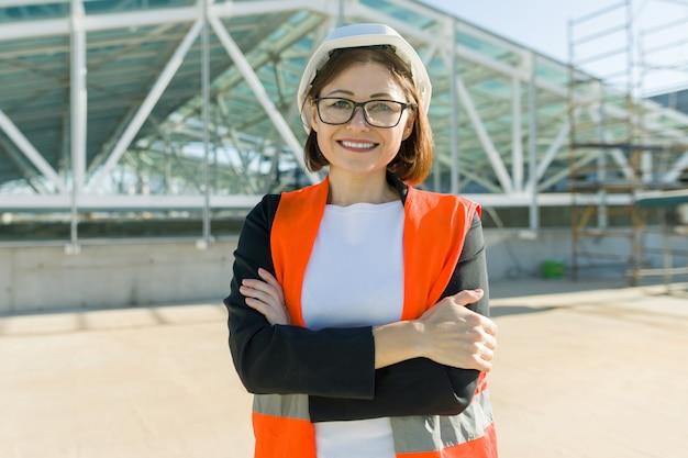 Portret van volwassen architectenvrouw bij een bouwwerf